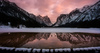 Frozen Toblachersee lake near Toblach, Italy, with Dolomites mountains and their reflection on unfrozen part of the lake on Saturday, 12th of March 2016.